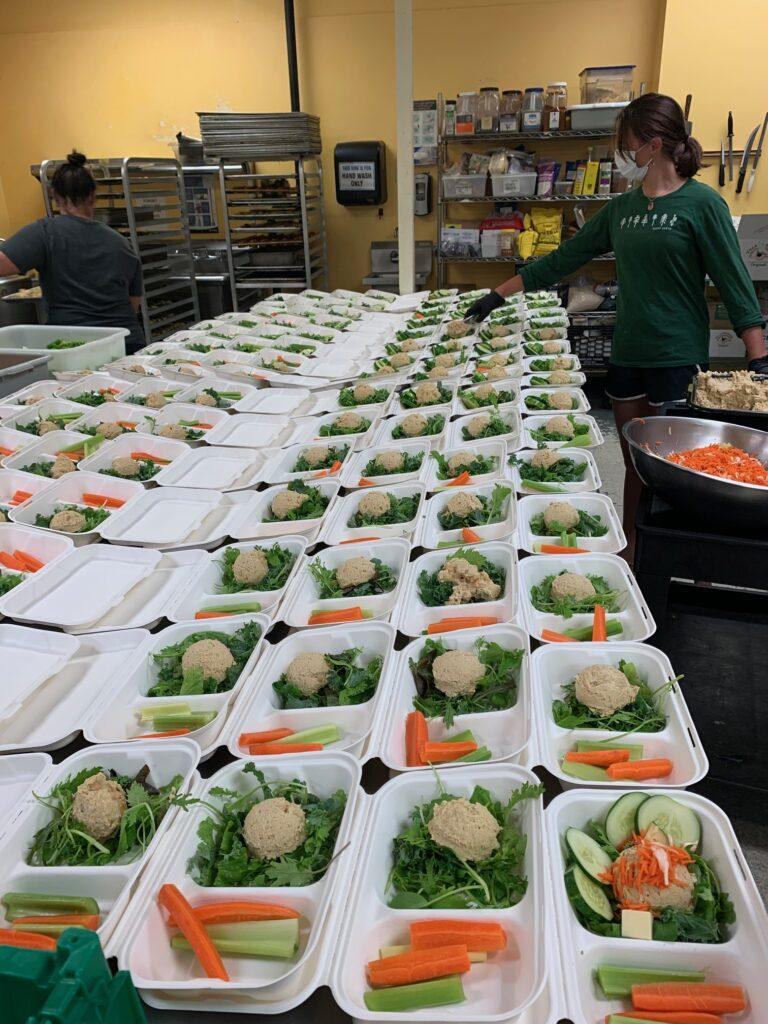 Sugarsnap employees pack dozens of food containers in commercial kitchen.